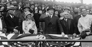 President Coolidge throwing out the first pitch while his wife looks on.