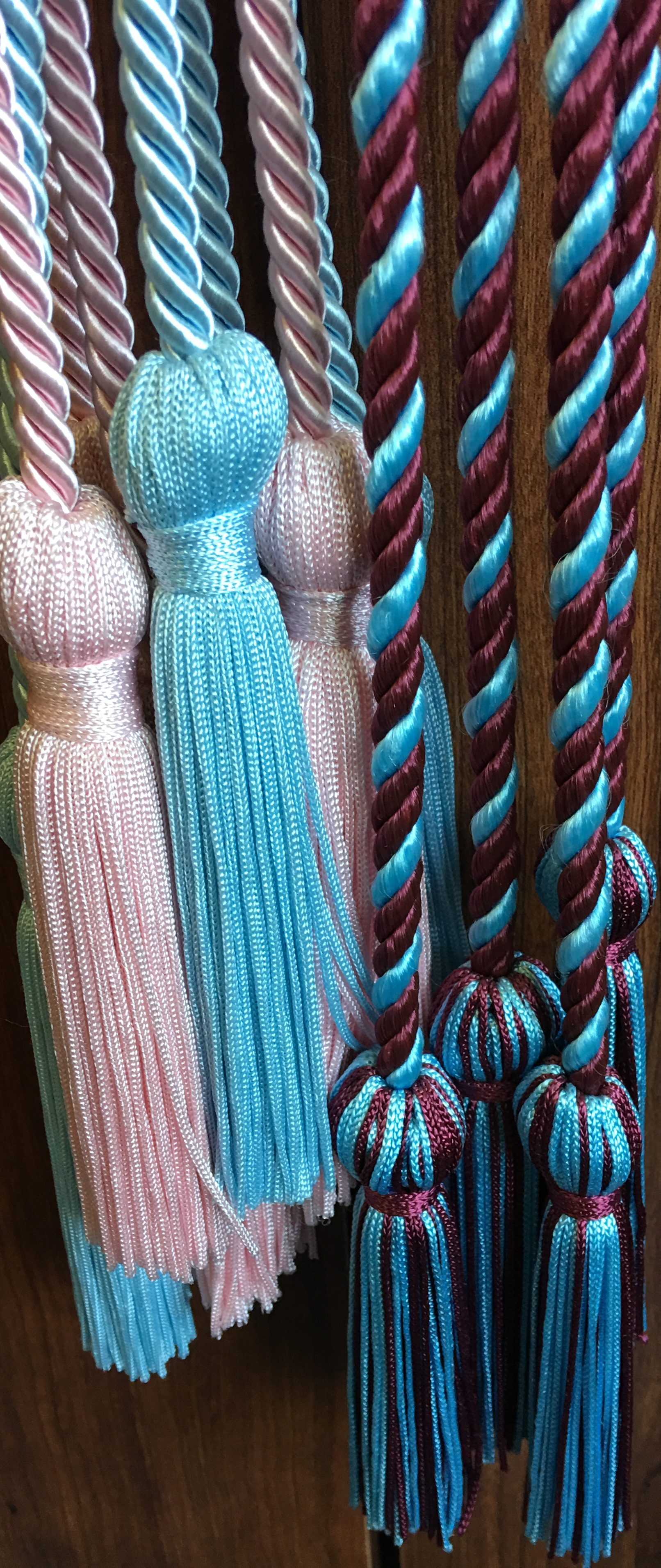 The tradition of wearing GLO stoles and cords has caught on in the last few decades. The cords are usually intertwined lengths of cording in the GLO's colors. Some of the stoles are simple with just the Greek letters. Others have chapter names and the graduate's name embroidered on it.